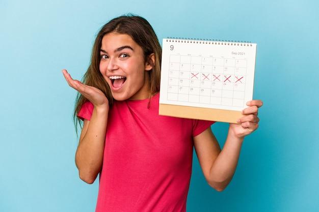 Junge kaukasische frau, die einen kalender auf blauem hintergrund hält holding