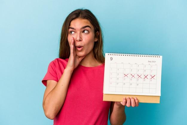 Junge kaukasische frau, die einen kalender auf rosa hintergrund hält, sagt eine geheime heiße bremsnachricht und schaut beiseite