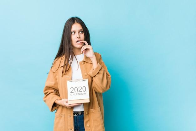Junge kaukasische frau, die einen kalender der 2020er jahre hält, entspannte das denken an etwas, das einen kopienraum betrachtet.