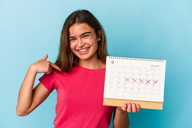 Junge kaukasische frau, die einen kalender einzeln auf rosafarbenem hintergrund hält, der mit der hand auf einen hemdkopierraum zeigt, stolz und selbstbewusst