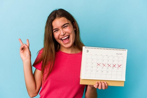 Junge kaukasische frau, die einen kalender einzeln auf rosafarbenem hintergrund hält, freudig und sorglos, der ein friedenssymbol mit den fingern zeigt.