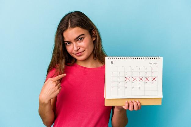 Junge kaukasische frau, die einen kalender einzeln auf rosafarbenem hintergrund hält und mit dem finger auf sie zeigt, als ob sie einladen würde, näher zu kommen.