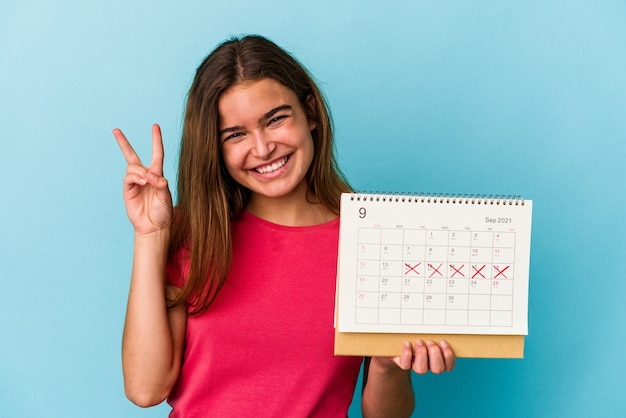 Junge kaukasische frau, die einen kalender hält, der auf rosa hintergrund isoliert ist und nummer zwei mit den fingern zeigt.