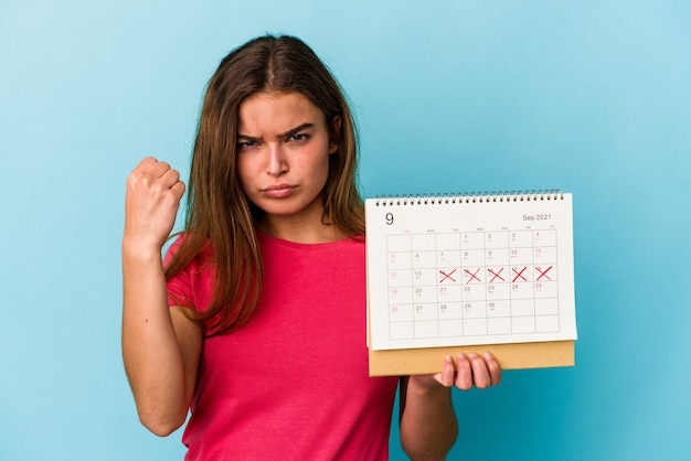 Junge kaukasische frau, die einen kalender hält, der auf rosafarbenem hintergrund isoliert ist und die faust zur kamera zeigt, aggressiver gesichtsausdruck.