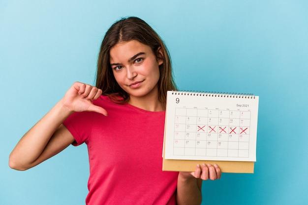 Junge kaukasische frau, die einen kalender hält, der auf rosafarbenem hintergrund isoliert ist und eine abneigungsgeste zeigt, daumen nach unten. meinungsverschiedenheit konzept.