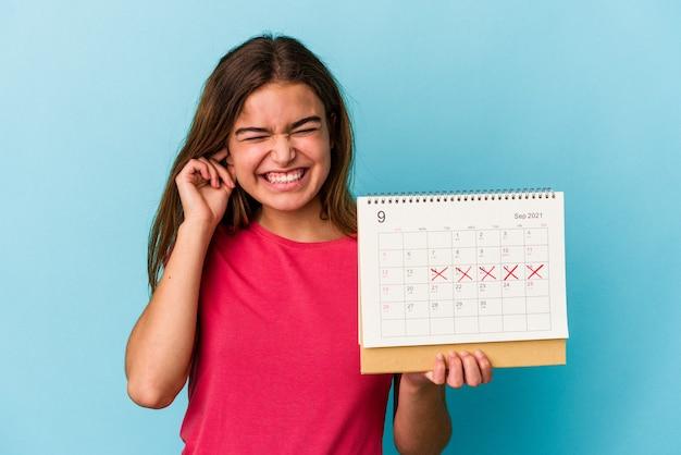 Junge kaukasische frau, die einen kalender lokalisiert auf rosa hintergrund hält, der ohren mit den händen bedeckt.