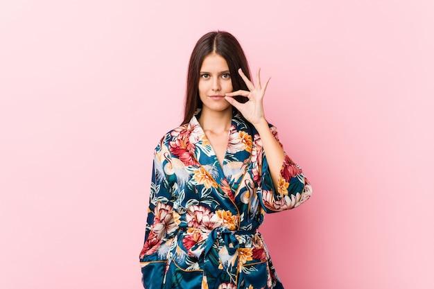 Junge kaukasische frau, die einen kimono-pyjama mit den fingern auf den lippen hält ein geheimnis trägt.