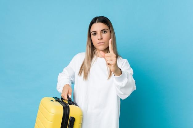 Junge kaukasische frau, die einen koffer hält, der nummer eins mit finger zeigt.