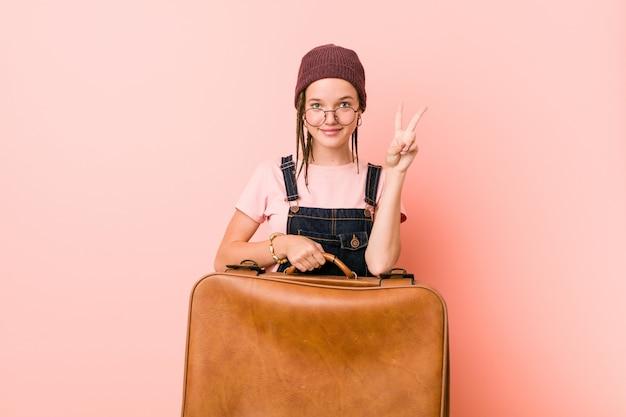 Junge kaukasische frau, die einen koffer hält, der nummer zwei mit den fingern zeigt.
