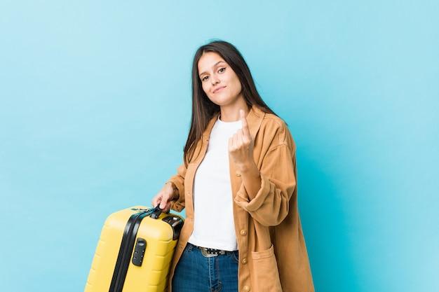 Junge kaukasische frau, die einen koffer zeigt mit dem finger auf sie hält, als ob einladung näher kommen.