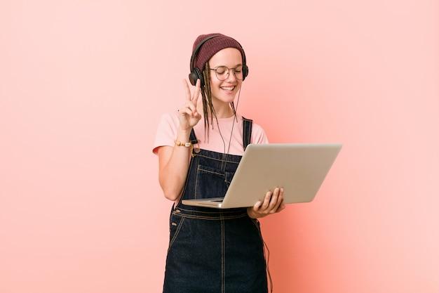 Junge kaukasische frau, die einen laptop hält, der nummer zwei mit den fingern zeigt.