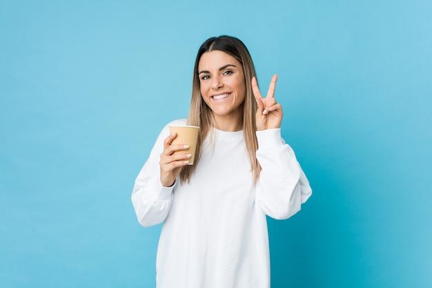 Junge kaukasische frau, die einen mitnehmerkaffee zeigt siegeszeichen und breit lächelt hält.