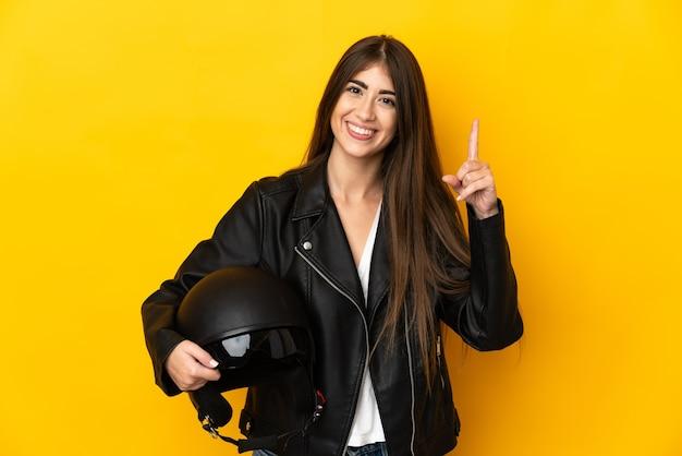 Junge kaukasische frau, die einen motorradhelm lokalisiert auf gelbem hintergrund hält, der einen finger im zeichen des besten zeigt und anhebt