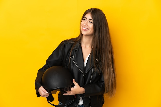 Junge kaukasische frau, die einen motorradhelm lokalisiert auf gelbem hintergrund hält, der zur seite schaut und lächelt