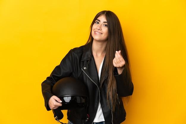 Junge kaukasische frau, die einen motorradhelm lokalisiert auf gelber wand hält, die geldgeste macht