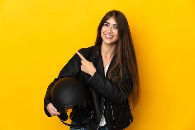 Junge kaukasische frau, die einen motorradhelm lokalisiert auf gelber wand hält, die zur seite zeigt, um ein produkt zu präsentieren