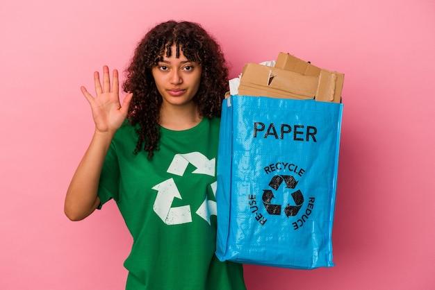 Junge kaukasische frau, die einen recycelten kunststoff hält, der auf rosafarbenem hintergrund isoliert ist, lächelt fröhlich und zeigt nummer fünf mit den fingern.