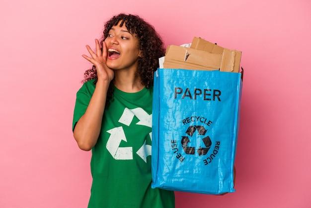 Junge kaukasische frau, die einen recycelten kunststoff hält, der auf rosafarbenem hintergrund isoliert ist, schreit und palme in der nähe des geöffneten mundes hält