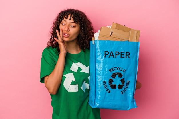 Junge kaukasische frau, die einen recycelten kunststoff isoliert auf rosa hintergrund hält, sagt eine geheime heiße bremsnachricht und schaut beiseite