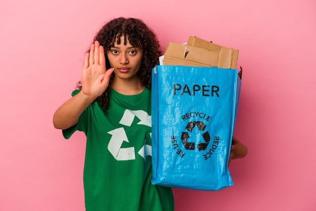Junge kaukasische frau, die einen recycelten kunststoff isoliert auf rosafarbenem hintergrund hält, der mit ausgestreckter hand steht und ein stoppschild zeigt, was sie verhindert