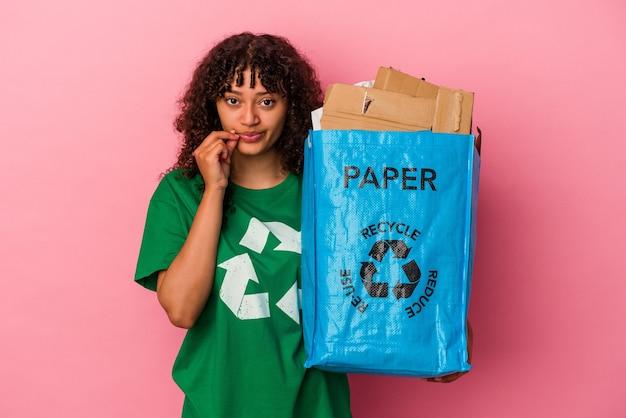 Junge kaukasische frau, die einen recycelten kunststoff lokalisiert auf rosa wand mit den fingern auf den lippen hält, die ein geheimnis halten.