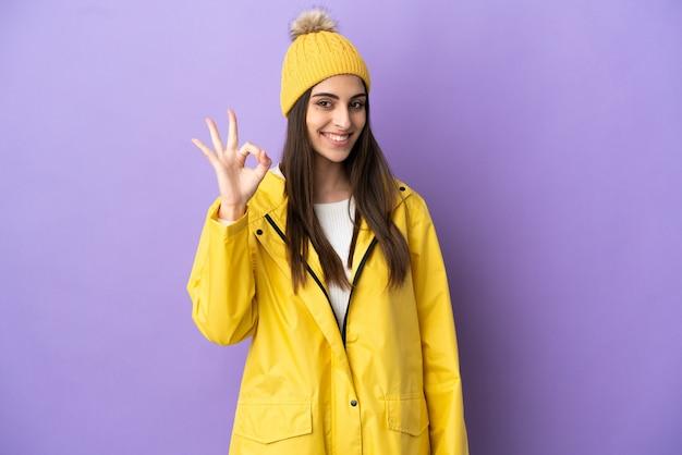 Junge kaukasische frau, die einen regendichten mantel trägt, der auf violettem hintergrund isoliert ist und ein ok-zeichen mit den fingern zeigt