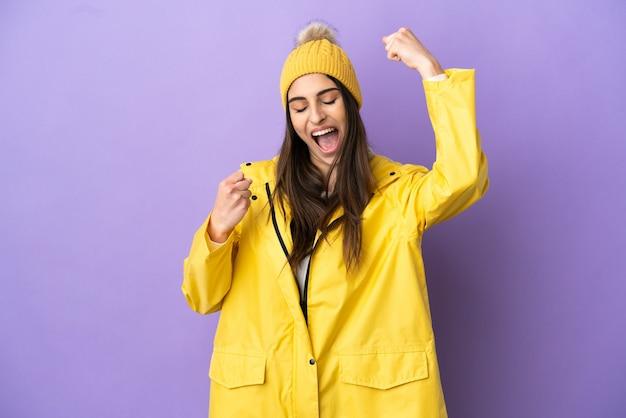 Junge kaukasische frau, die einen regendichten mantel trägt, isoliert auf violettem hintergrund, der einen sieg feiert?