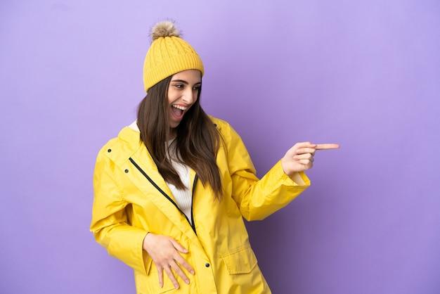 Junge kaukasische frau, die einen regendichten mantel trägt, isoliert auf violettem hintergrund, der mit dem finger zur seite zeigt und ein produkt präsentiert