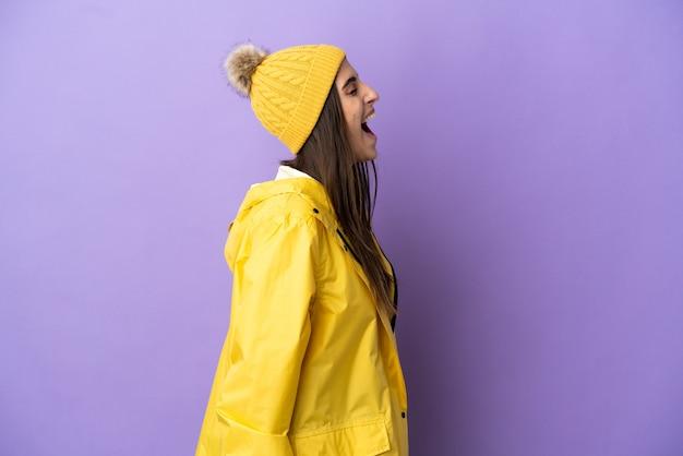 Junge kaukasische frau, die einen regendichten mantel trägt, isoliert auf violettem hintergrund, lacht in seitenlage