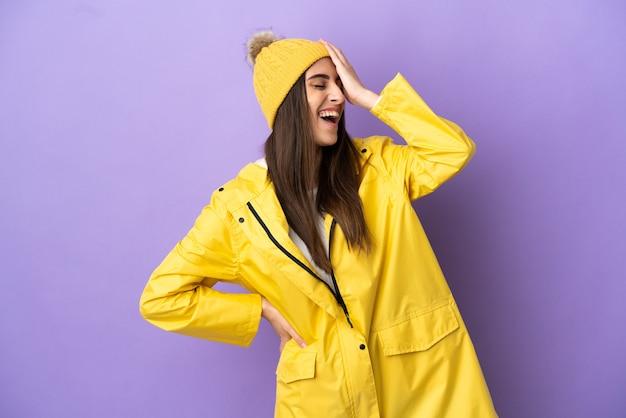 Junge kaukasische frau, die einen regendichten mantel trägt, isoliert auf violettem hintergrund, lächelt viel