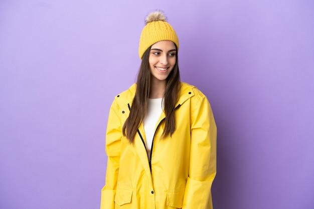 Junge kaukasische frau, die einen regenfesten mantel trägt, der auf purpurrotem hintergrund seitlich schaut