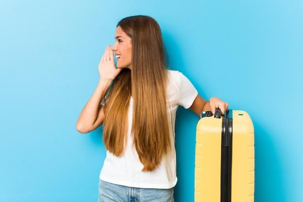 Junge kaukasische frau, die einen reisekoffer schreit und hält palme nahe geöffnetem mund hält.