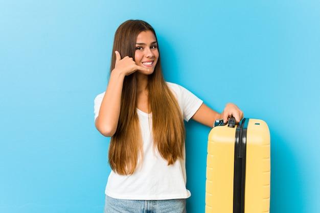 Junge kaukasische frau, die einen reisekoffer zeigt eine handyanrufgeste mit den fingern hält.