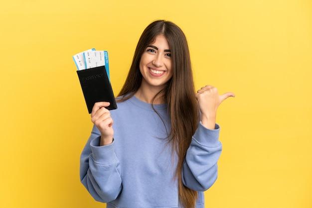 Junge kaukasische frau, die einen reisepass auf gelbem hintergrund hält, der auf die seite zeigt, um ein produkt zu präsentieren present