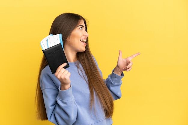 Junge kaukasische frau, die einen reisepass auf gelbem hintergrund hält, der mit dem finger zur seite zeigt und ein produkt präsentiert