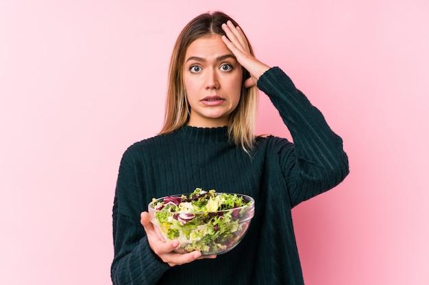 Junge kaukasische frau, die einen salat hält, der geschockt wird, sie hat sich an wichtiges treffen erinnert.