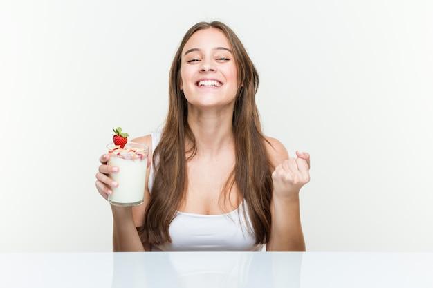 Junge kaukasische frau, die einen smoothie zujubelt sorglos und aufgeregt hält. sieg-konzept.