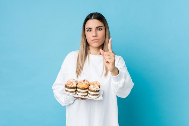 Junge kaukasische frau, die einen süßigkeiten-kuchen hält, der nummer eins mit finger zeigt.