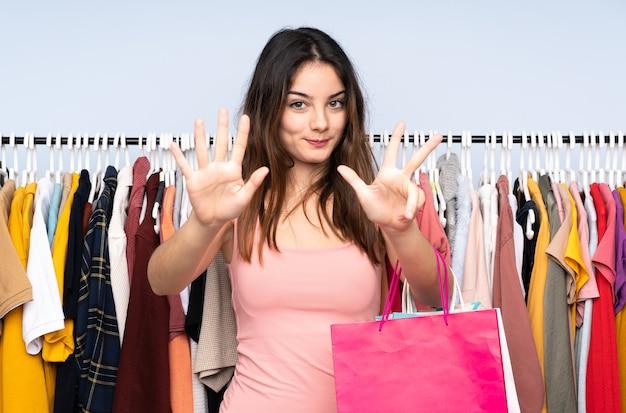 Junge kaukasische frau, die einige kleider in einem geschäft kauft