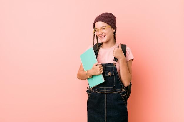 Junge kaukasische frau, die einige notizbücher hält, die lächeln und daumen hochheben
