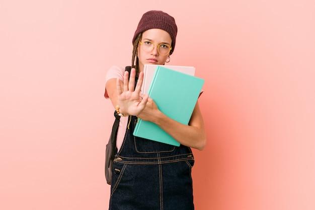 Junge kaukasische frau, die einige notizbücher hält, die mit ausgestreckter hand stehen, die stoppschild zeigt, das sie verhindert.