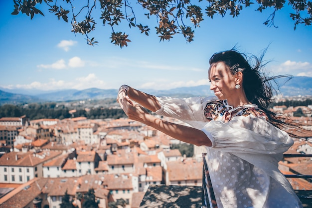 Junge kaukasische frau, die foto durch handy vom beobachtungsplatz macht