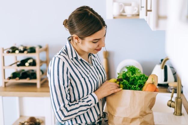 Junge kaukasische frau, die gemüse von einer papiereinkaufstasche in der küche nimmt.