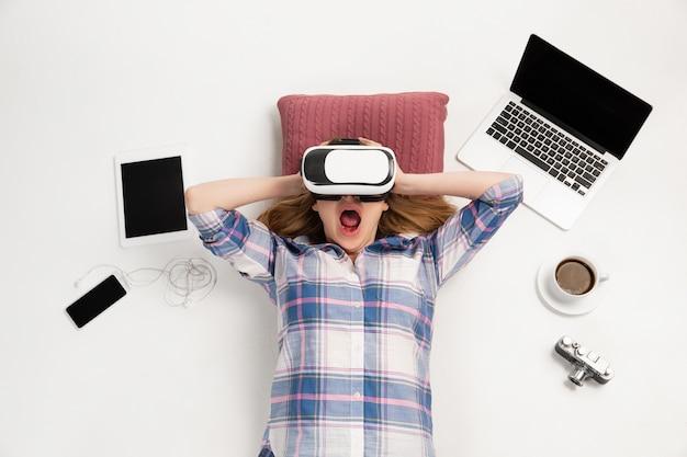 Junge kaukasische frau, die geräte, geräte lokalisiert auf weißer oberfläche verwendet. konzept moderner technologien, gadgets, technik, emotionen, werbung. exemplar. spielen, einkaufen, online-bildung treffen.