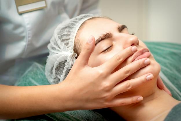 Junge kaukasische frau, die gesichtsmassage durch kosmetikerhände im medizinischen salon des spa erhält