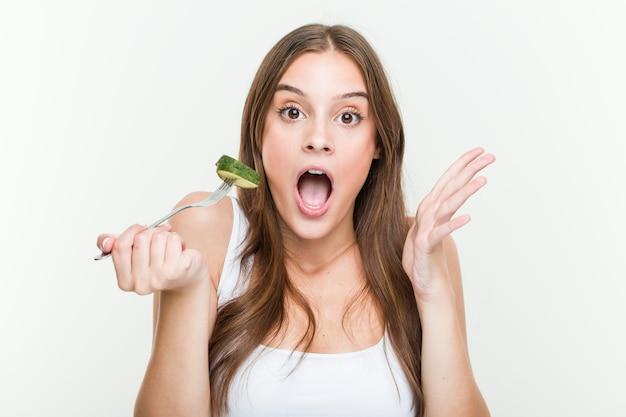 Junge kaukasische frau, die gurke isst, die einen sieg oder erfolg feiert