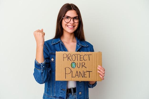 Junge kaukasische frau, die hält, beschützt unser planetenplakat isoliert stehend mit ausgestreckter hand, die stoppschild zeigt, das sie verhindert.