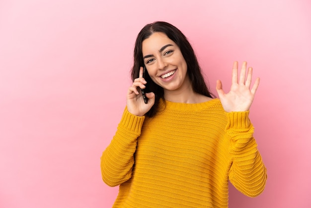 Junge kaukasische frau, die handy lokalisiert auf rosa hintergrund salutiert mit hand mit glücklichem ausdruck