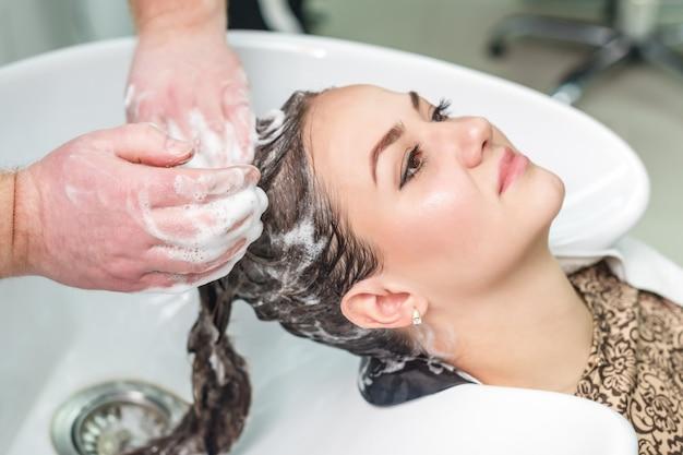 Junge kaukasische frau, die ihre haare wäscht.