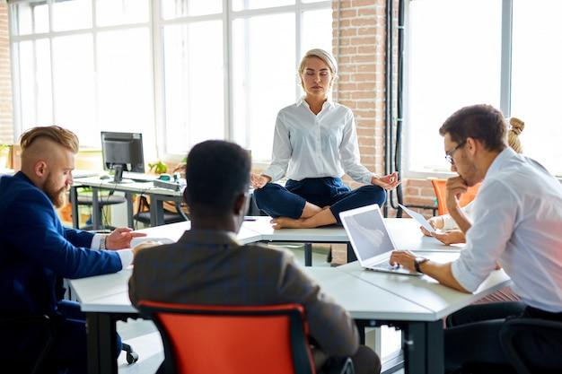 Junge kaukasische frau, die im büro meditiert, während kollegen arbeiten